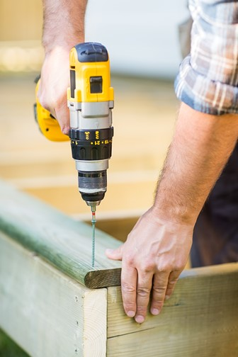 carpenter using a cordless drill to drill a hole
