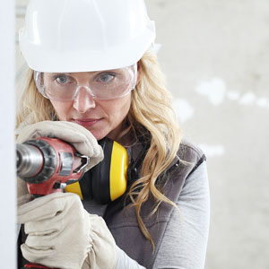 safety-conscious carpenter wearing safety glasses and gloves while drilling a hole in sheetrock